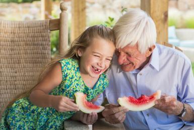 Caucasian man and granddaughter eating watermelon